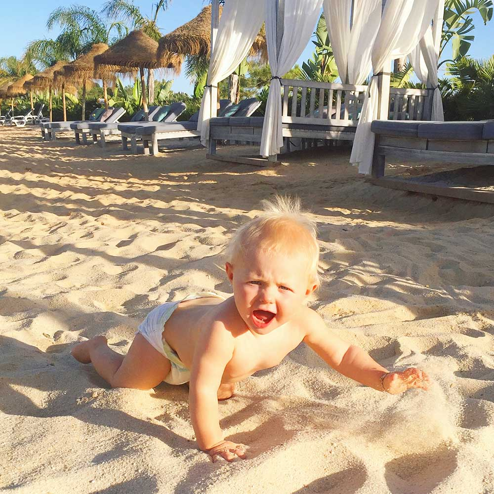 Rosie discovering the joy of sand beneath her feet at Quinto do Lago, Algarve.