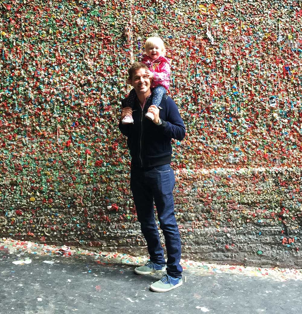 Rosie and Justin in front of the famous Gum Wall at Pike Place Market in Seattle.