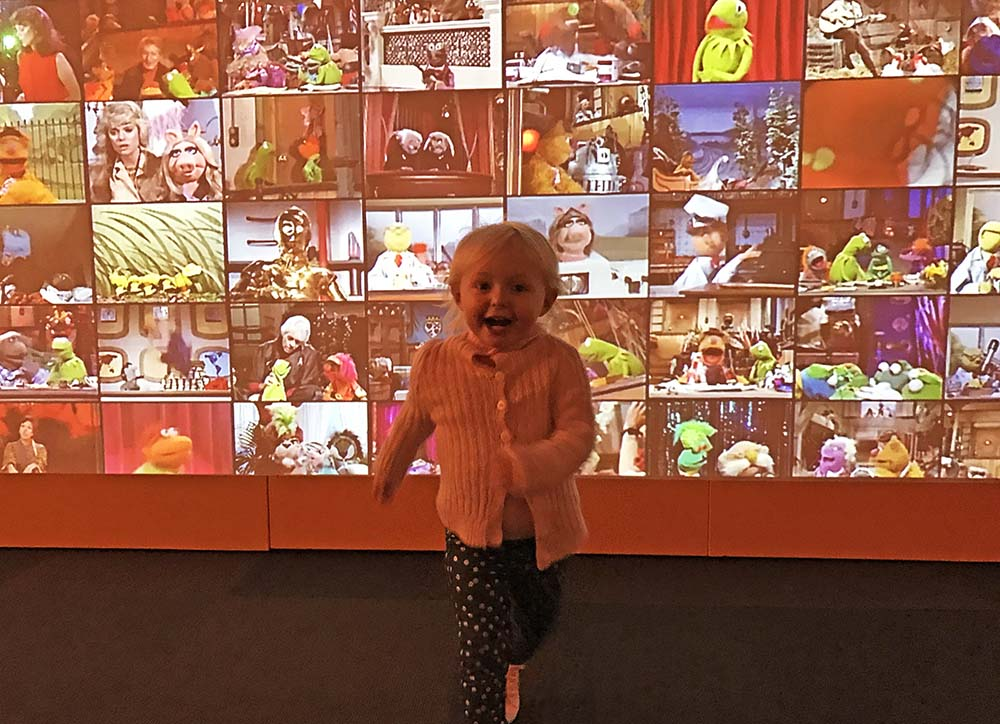 Rosie experiencing pure joy in front of the Muppet movie installation at The Museum of Pop Culture.