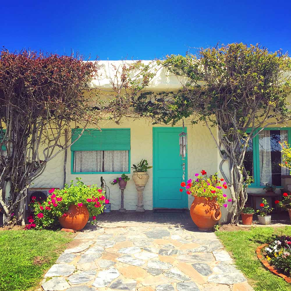 November 2016: Jose Ignacio, Uruguay.  We spotted this sweet beach house on a bicycle ride around this sleepy town. I loved the colorfully painted windows and doors, abundant greenery, potted flowers, and bright blue sky as a backdrop.