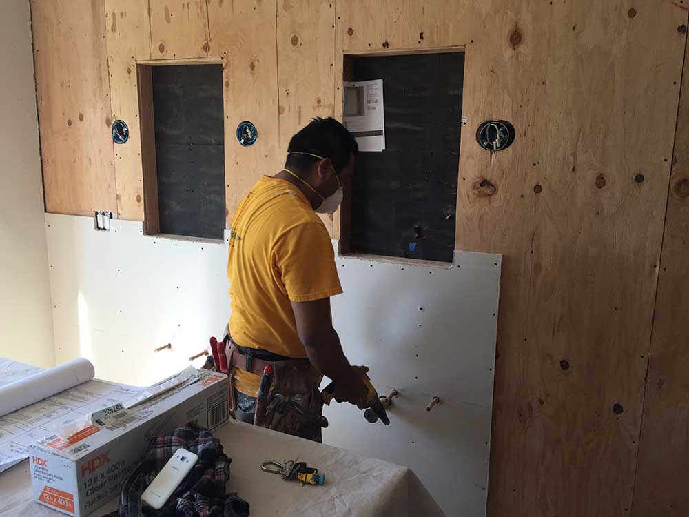 Preparing the cavities for the recessed medicine cabinets, and the electric for the mounted light fixtures.