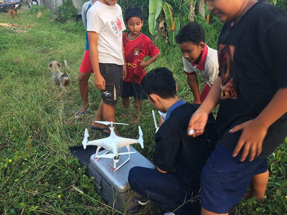 I love this photo showing the drone pilot surrounded by all the neighborhood kids, eager to see it take off.