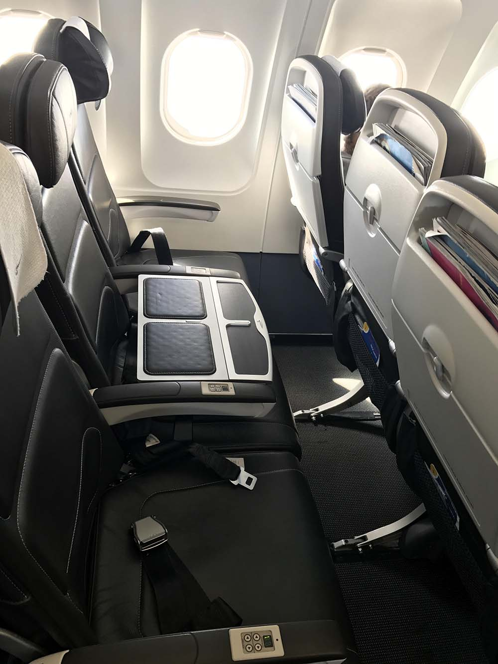 """A row of three seats in Business class, with the middle seat being used to separate passengers. Only the two seats on either side of the """"table seat"""" are available to"""