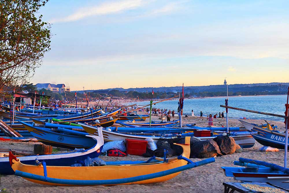 Traditional fishing boats lined up along Jimbaran Beach in front of the fish market.
