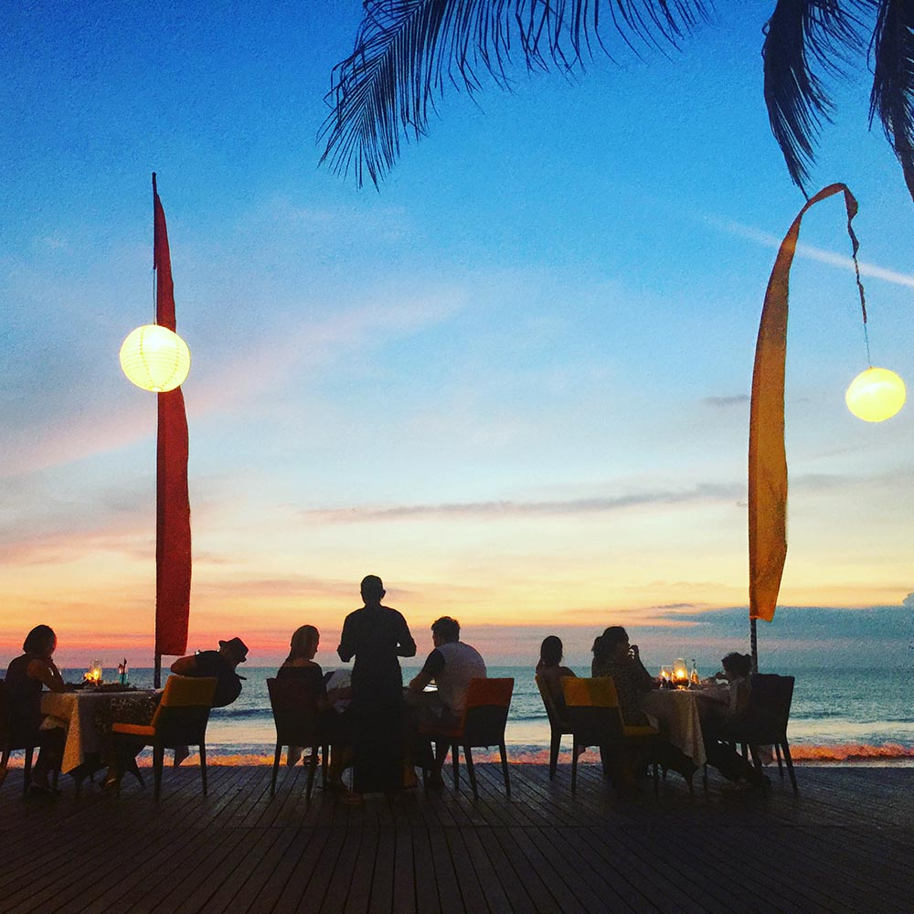 Cocktails while the sun sets over Seminyak Beach.