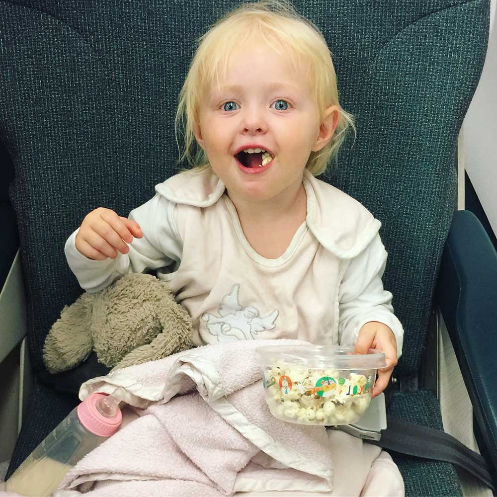 Rosie snacking on popcorn, in her pajamas, while we wait for takeoff.