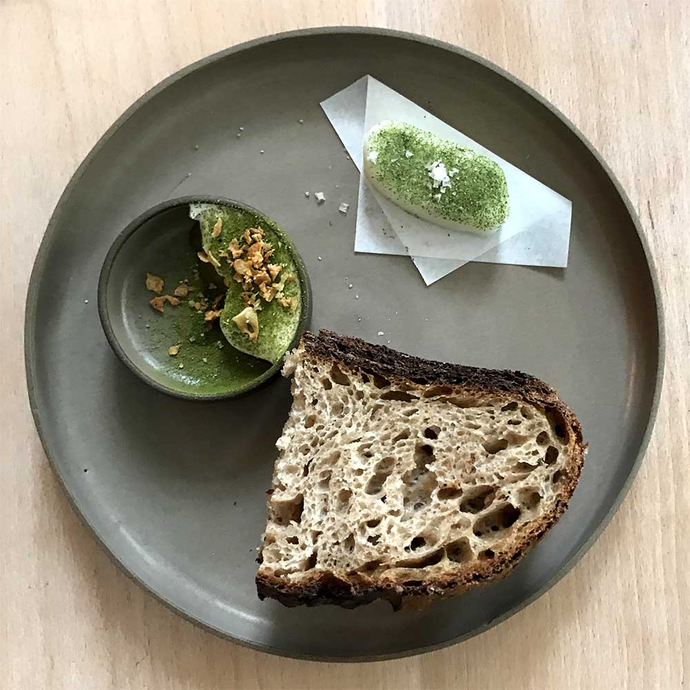 The wheat bread at Prado is served with with fresh goats butter with smoked salt and sea lettuce, and whipped Iberico port fat with garlic and bay leaf.