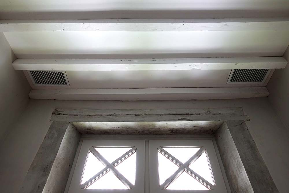 The first air conditioning vents being installed in the ceiling, before the plastering has been finished.