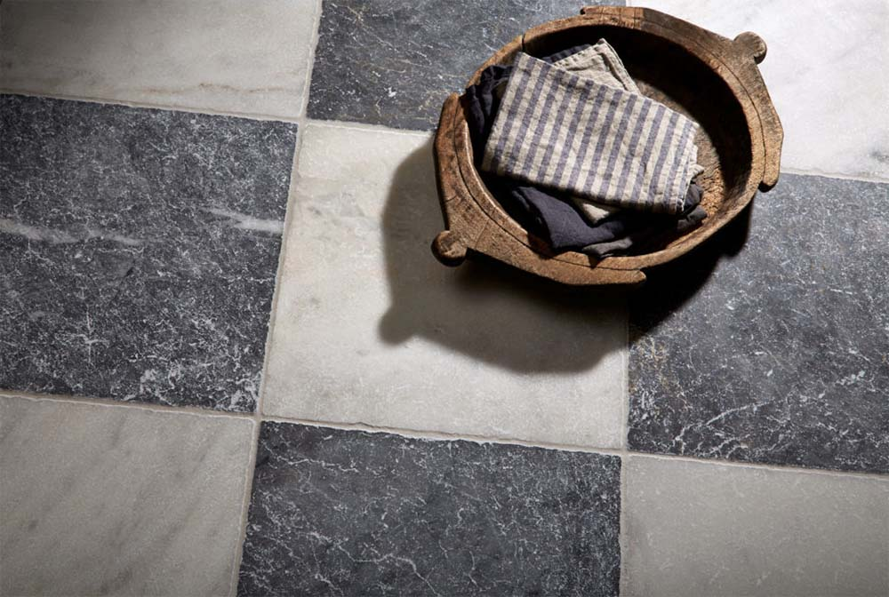 Tumbled black and white marble tiles. Image via  Mandarin Stone .