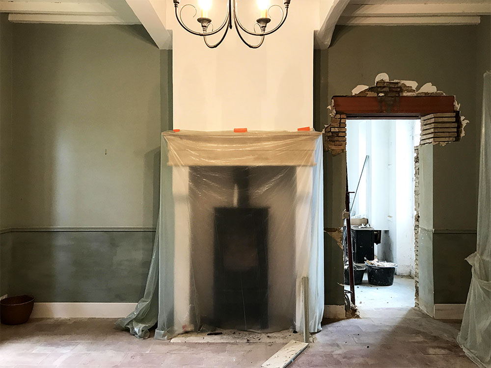 The previous owners were using this room as a library, but we will be using it as our family dining room. We're creating symmetrical glass doorways, on either side of the fireplace, that will open into the orangerie. It's going to be so much nicer to be able to access the orangerie from the main house. Another bonus is all the extra light it lets into this room.