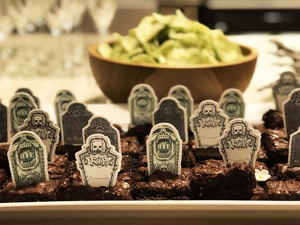 I enjoyed making this chocolate brownie graveyard, adorned with edible tombstone wafers and sugar flowers. Behind there is a bowl of green 'Frankenstein' wasabi-flavoured crisps.