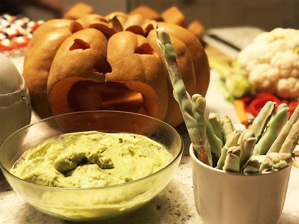 A pumpkin vomiting guacamole, and a jar of green witches fingers.