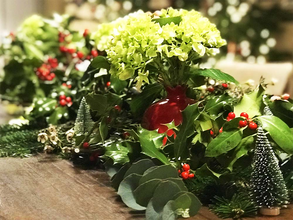 Our tablescape; lots of holly and red berries, pine branches and mini Christmas trees.