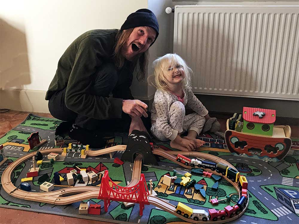 Playing with her new train set with Uncle B.