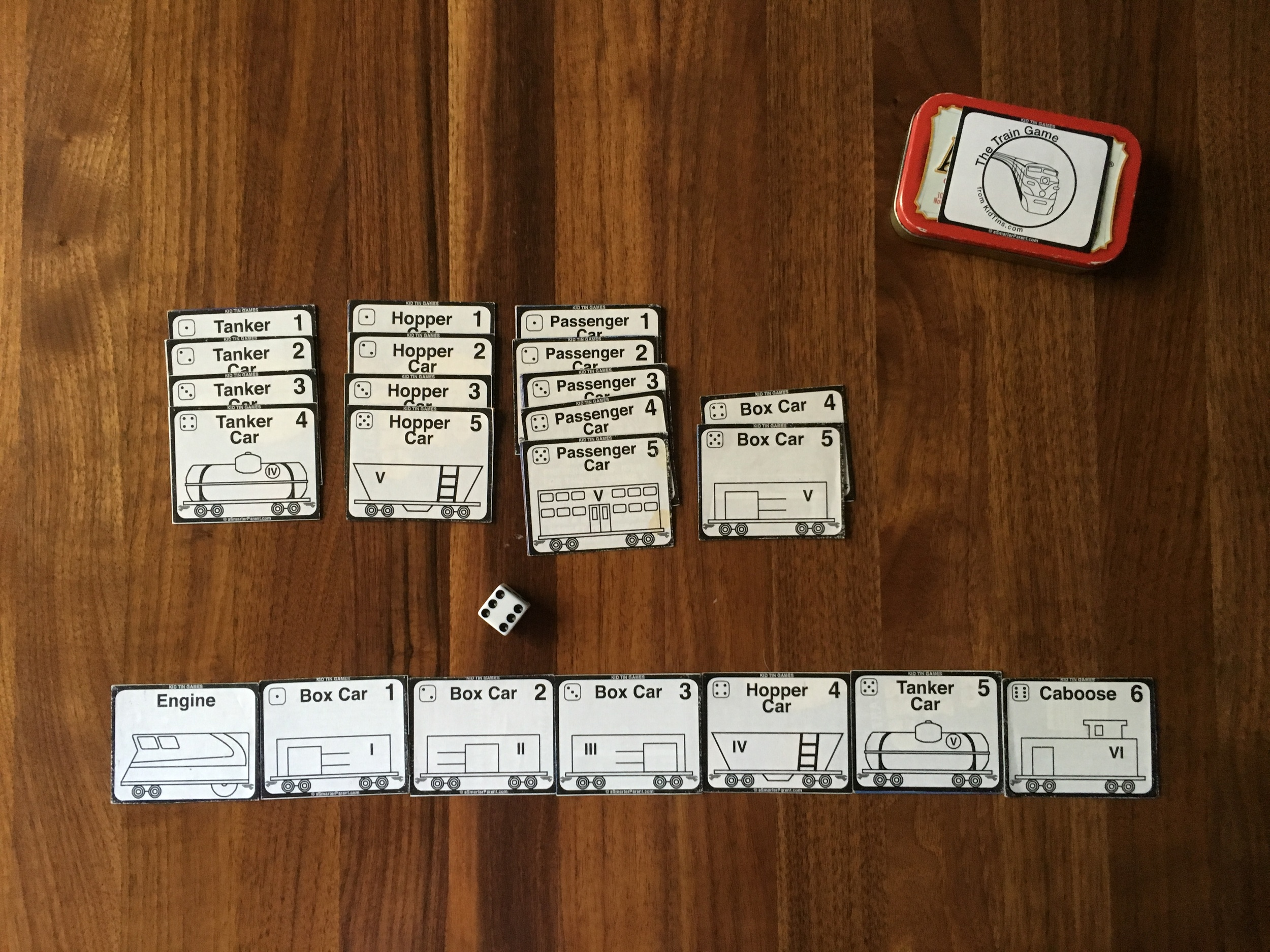 Assemble your train (cars #1-5), then roll for a 6 to win!