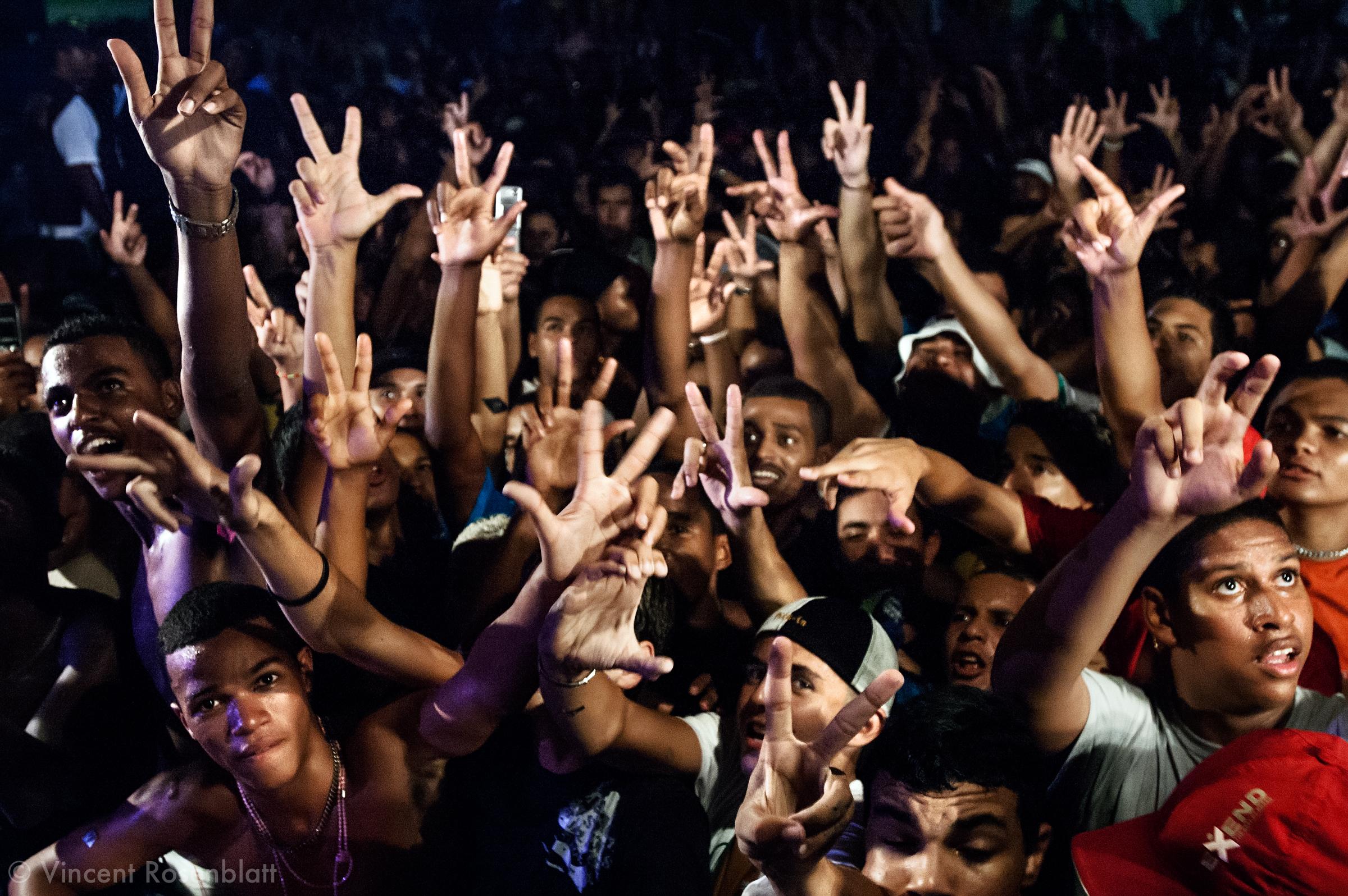 """Description/Caption:""""Baile"""" of Furacão Tsunami, the most powerful soundsystem on the Funk scene in Rio. Club Boqueirão, downtown Rio de Janeiro . Every hand gesture has a meaning : 3 fingers apart mean """"Vida louca"""" (crazy life), the C and V letters symbolize the Commando Vermelho, the principal drug faction in Rio's favelas."""