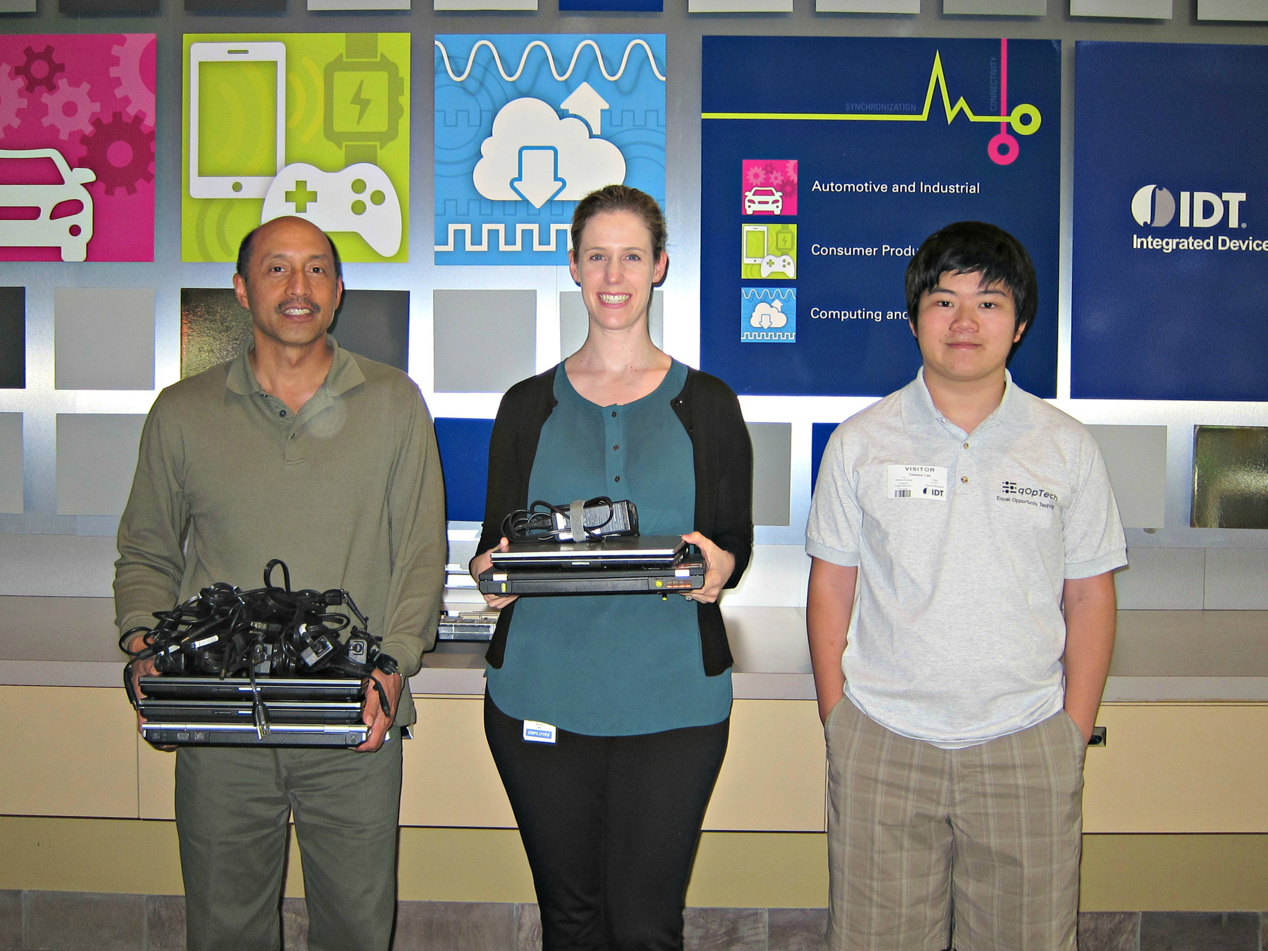 Robert Venenciano and Kristina Bullock from IDT presenting donated laptops to Terence Lee, EqOpTech (left to right)