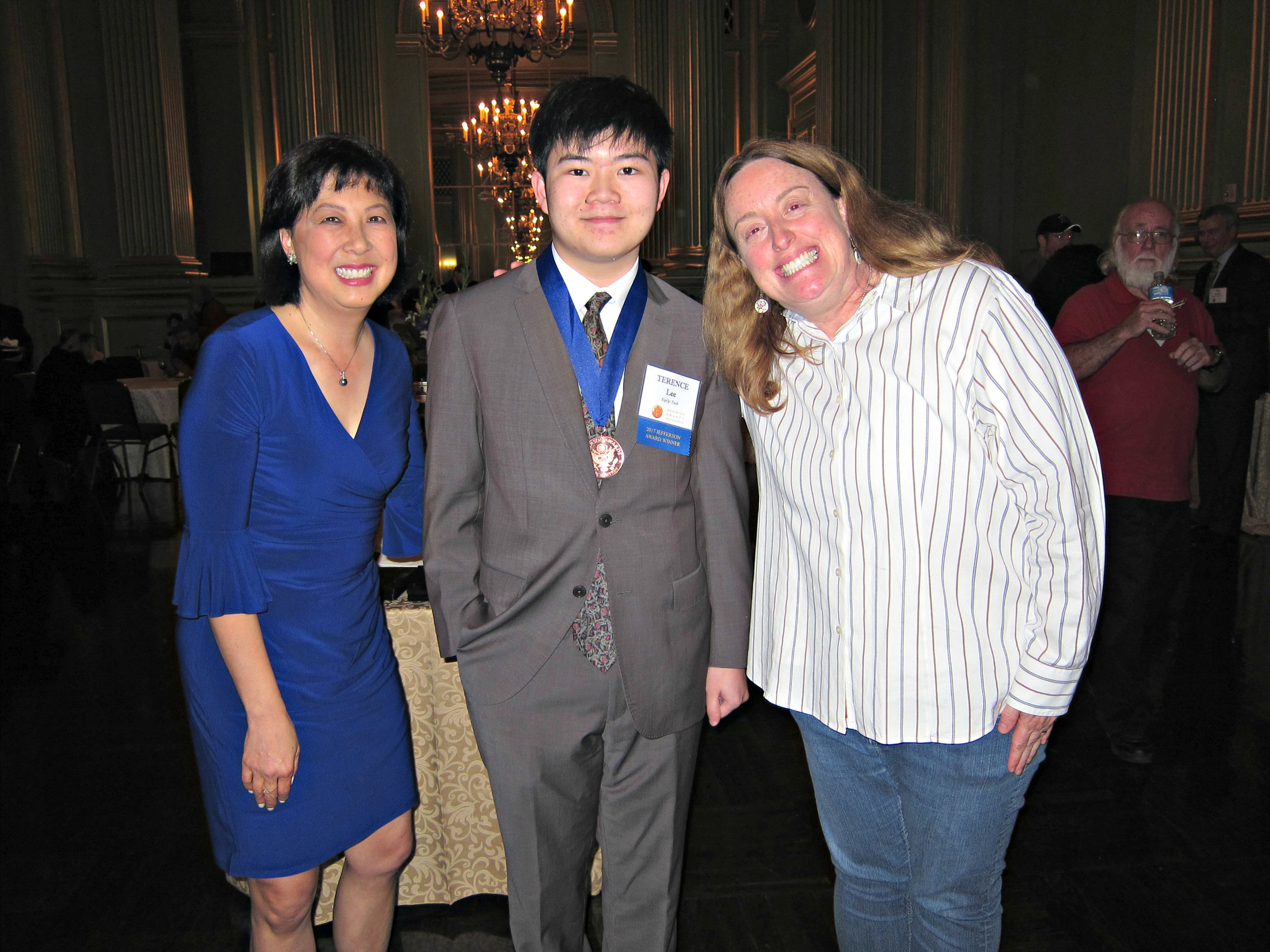 Terence Lee, center, wearing his Jefferson Award Medal, is flanked by CBS KPIX, Sharon Chin, left, and Jennifer Mistrot