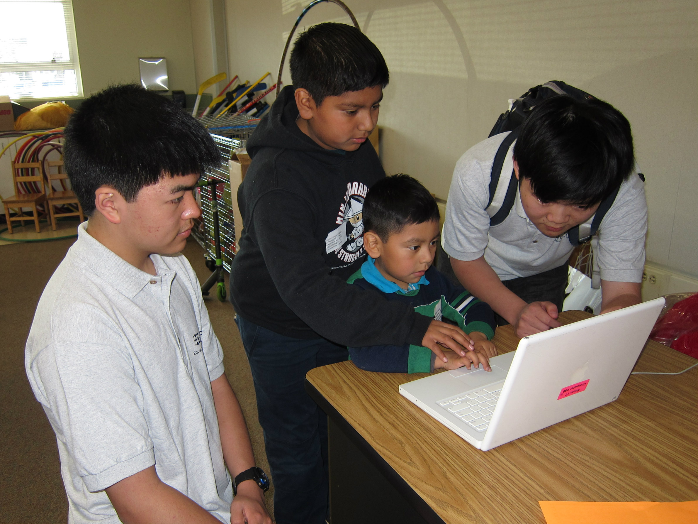 EqOpTech student leaders providing orientation to student on his first refurbished laptop