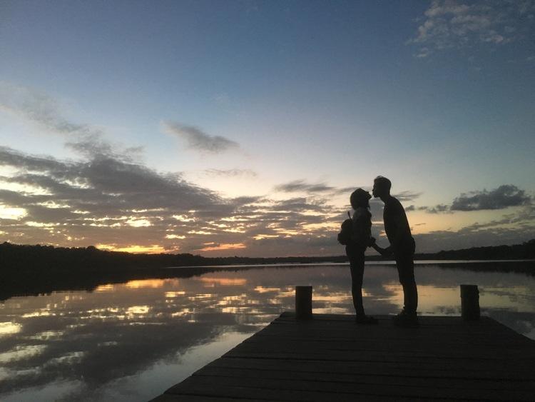 Couple kissing under sunset