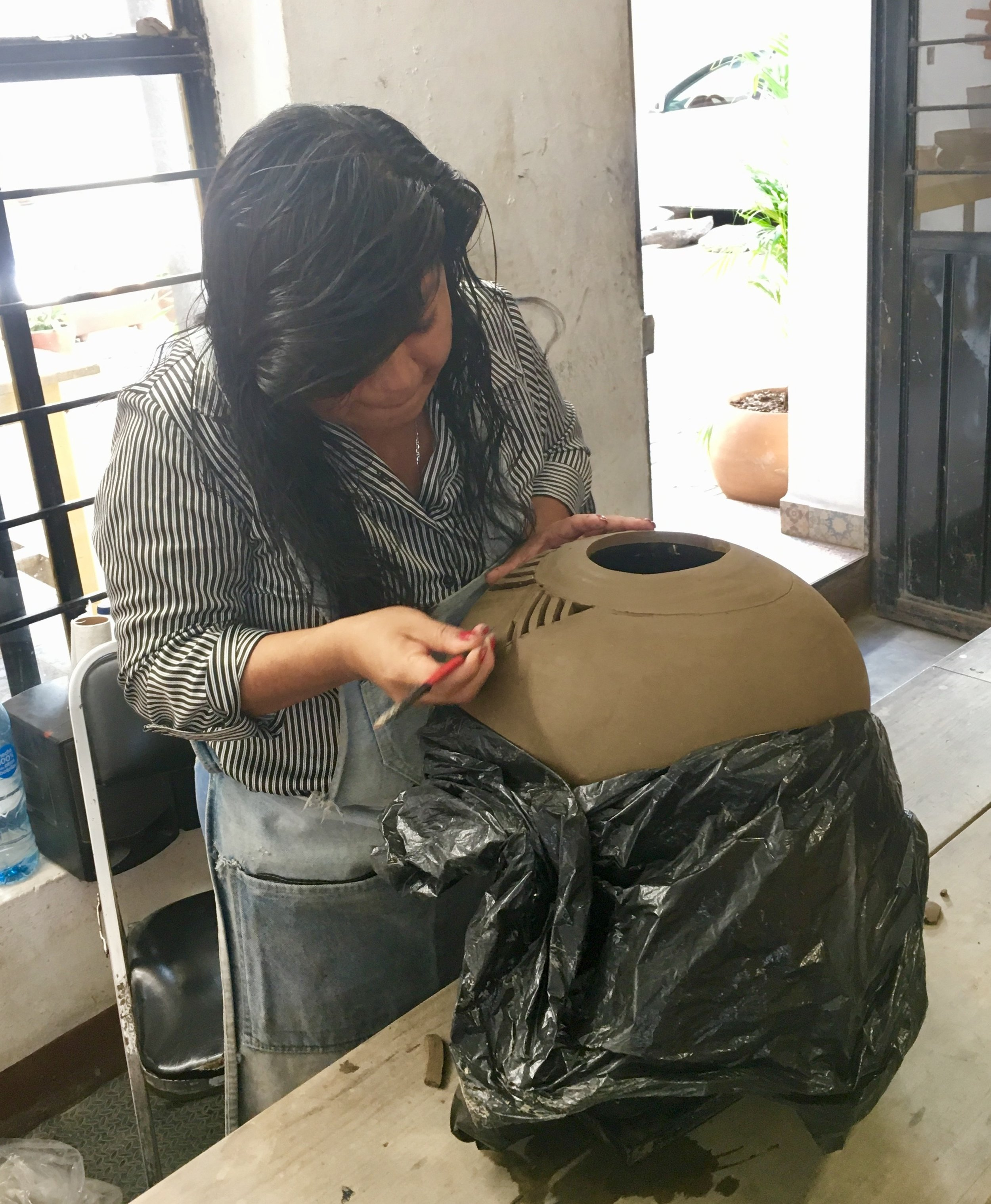 Woman carving clay pottery Oaxaca Mexico