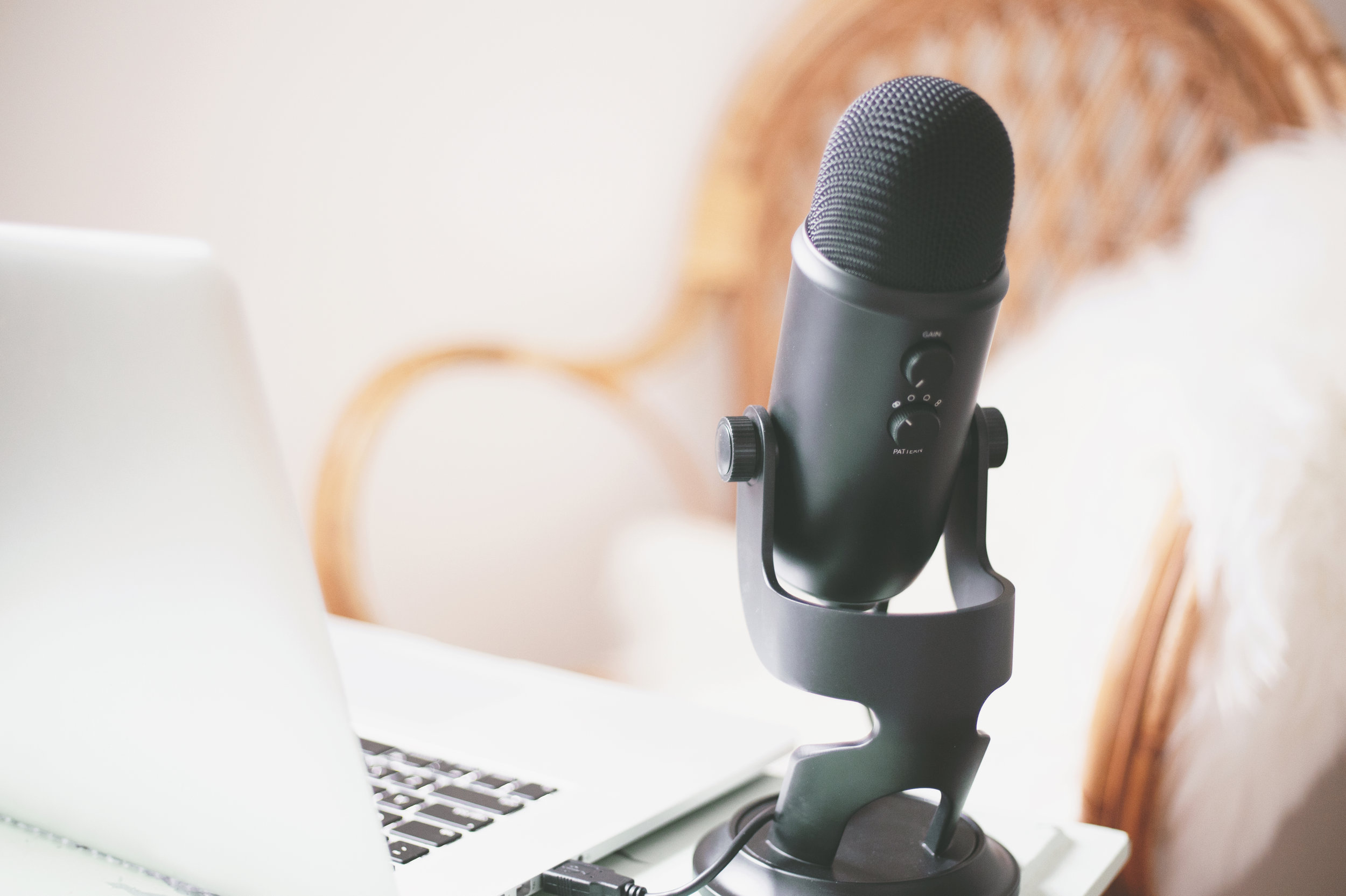 A USB microphone and a laptop, ready to go to start a podcast