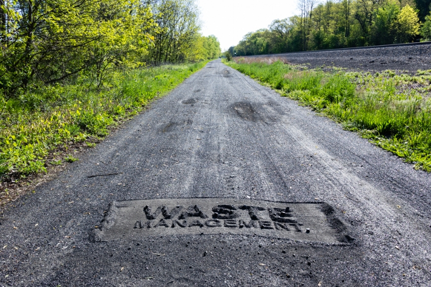 Waste Management (the road)  2016, coal ash lettering on coal ash covered roadbed in Pines, Indiana