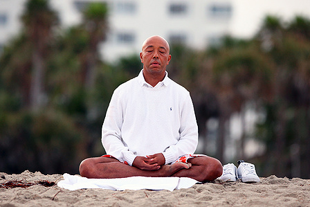 Russell Simmons meditating on the beach. Image via Success Story Nework.