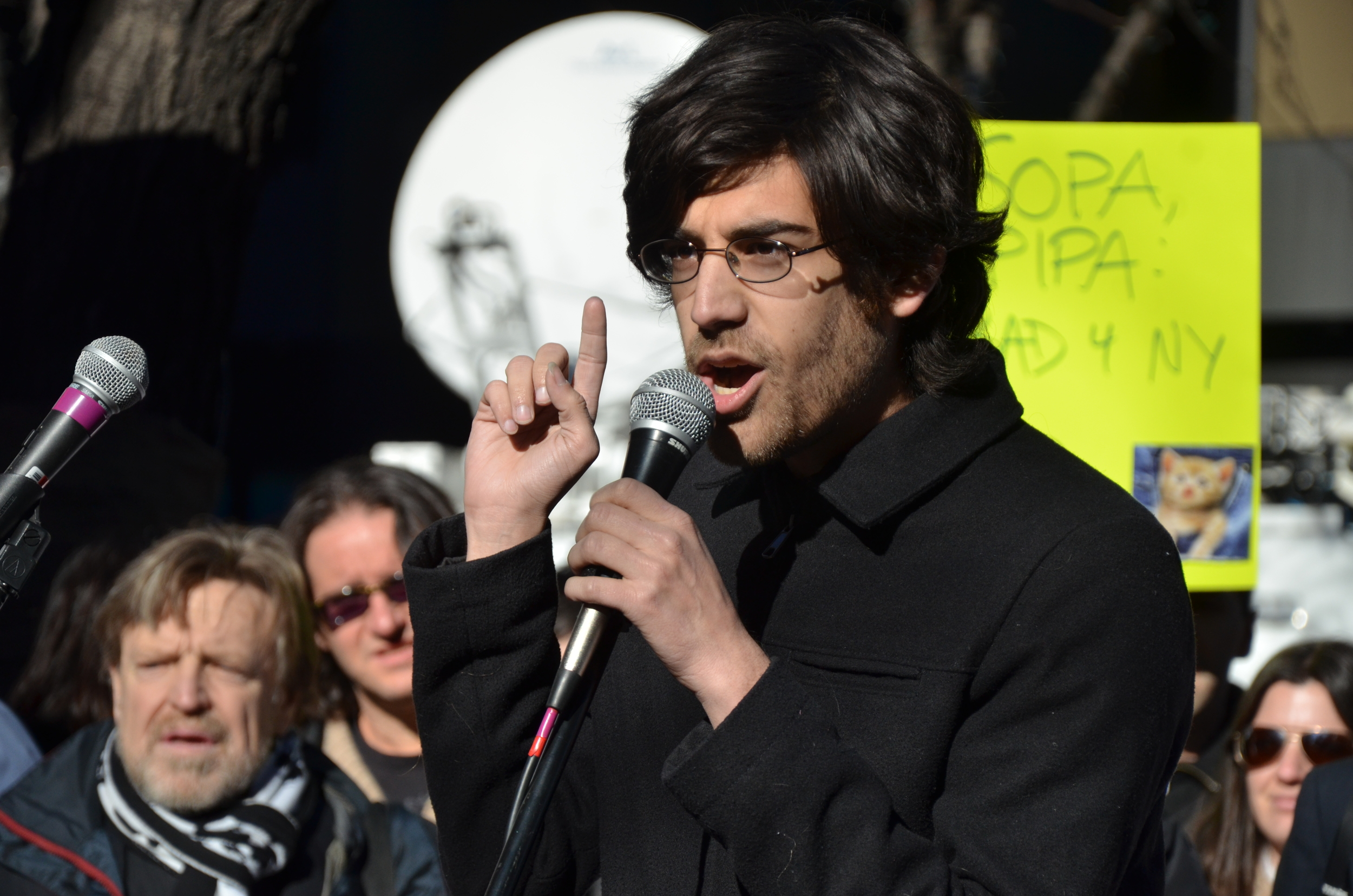 2012 - Swartz protesting against the Stop Online Piracy Act (SOPA) a year before his suicide. In the background, on the left corner, is Grateful Dead lyricist, John Perry Barlow.