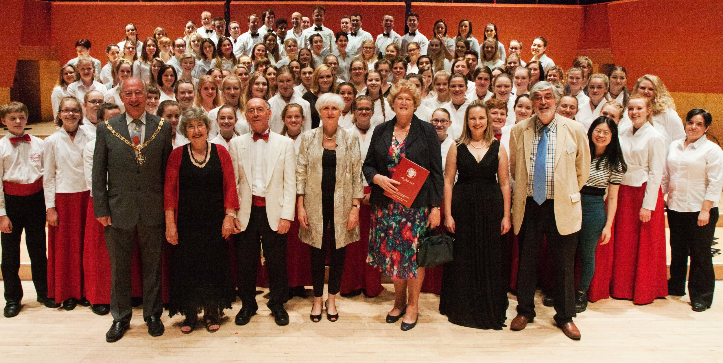 Farnham Youth Choir & Alumni Choir stand alongside the founders David & Gillian Victor-Smith (second and third left), accompanist Julia Freeman (centre), Choral Director - Joanna Tomlinson (second right)and FYC Chairman, Graham Noakes (right) at the Celebration Concert, The Anvil Basingstoke - July 2016.