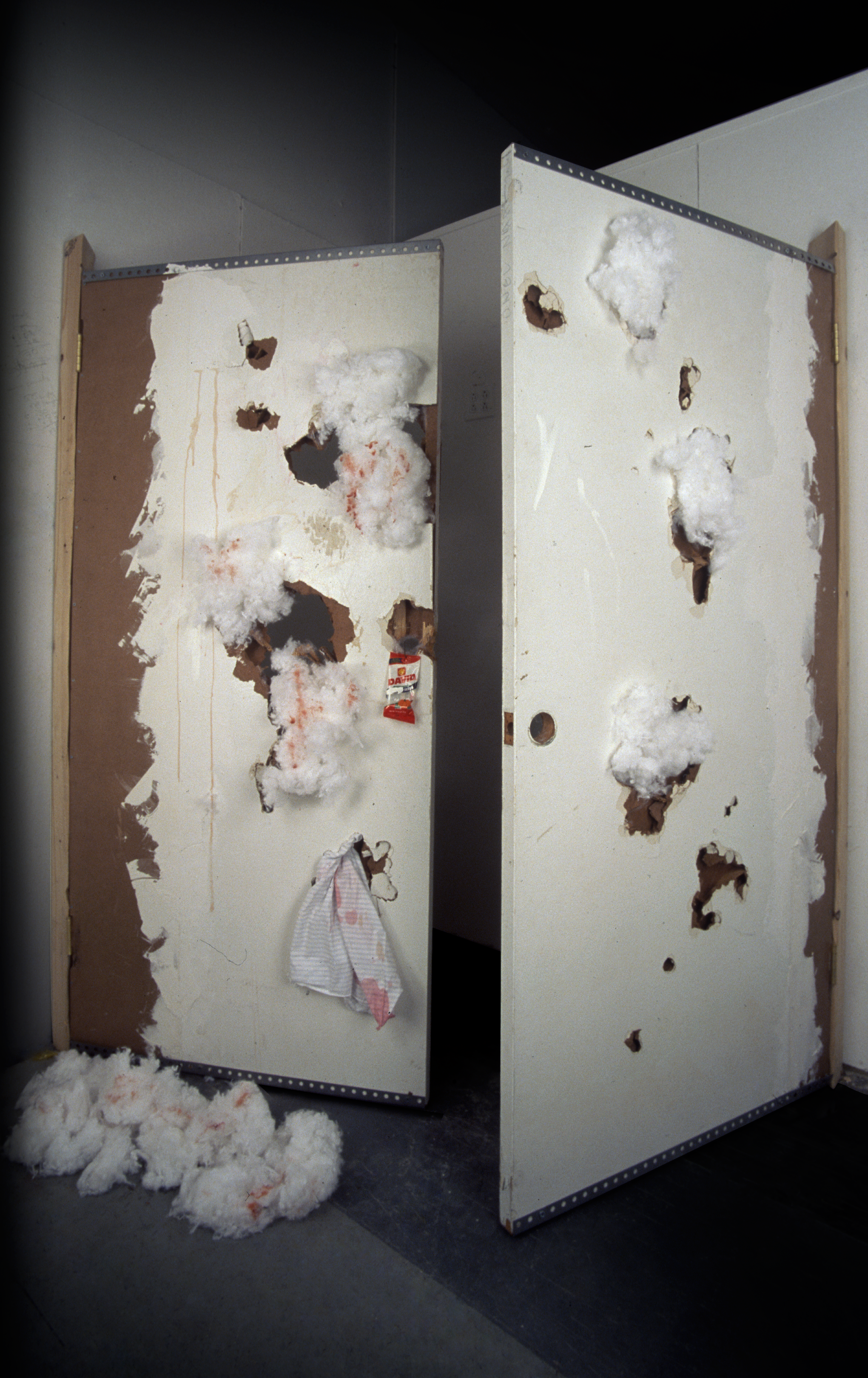 """""""David's Seeds""""  Chicken blood on cotton,  chicken blood on found doors,  cotton on found doors,  gesso on David Sunflower Seeds bag;  wood studs and hardware  Dimensions variable  2001"""