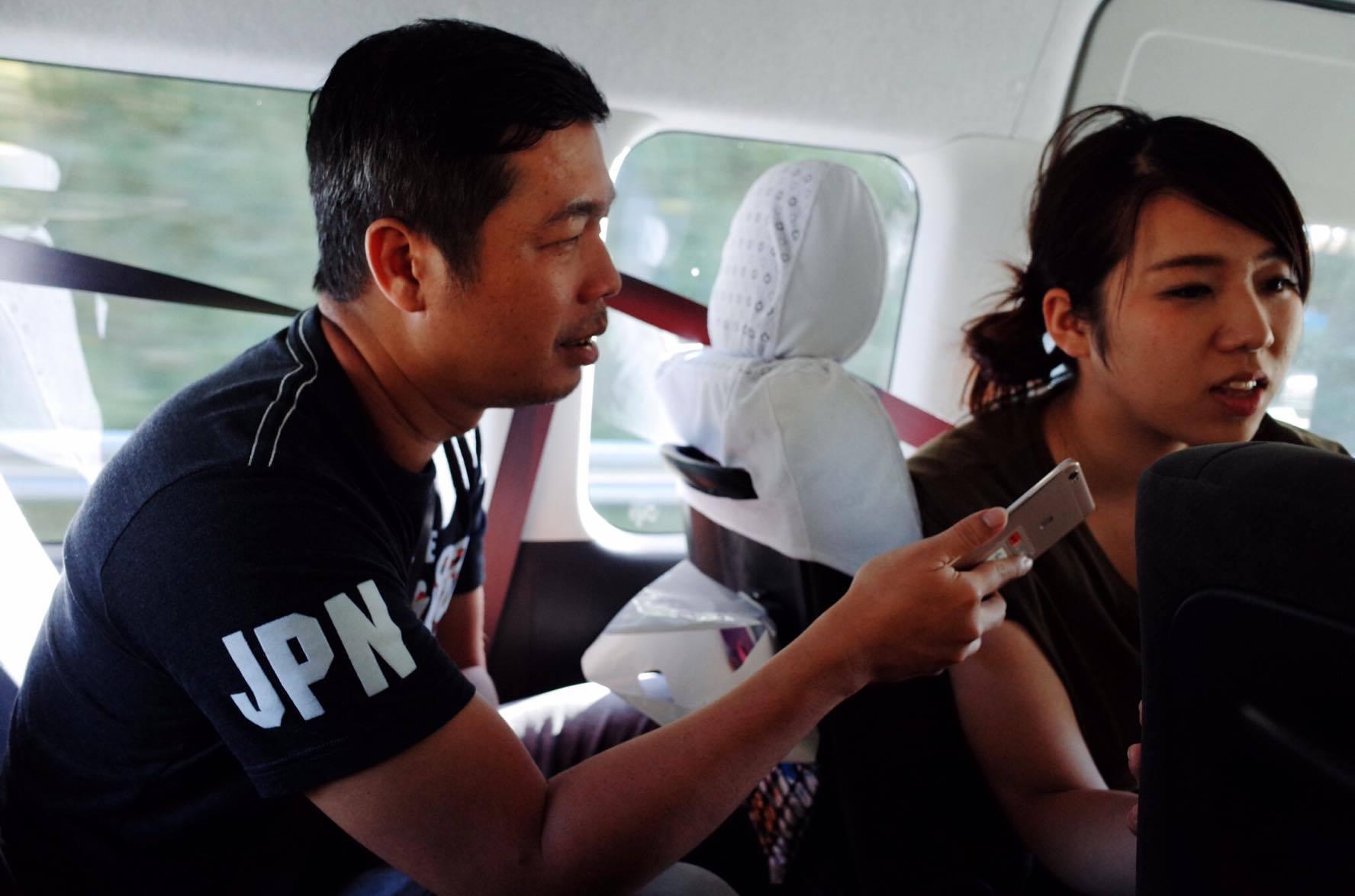 ウーさん(写真左)。帰りのバスではスマホも使いながらコミュニケーションしました。