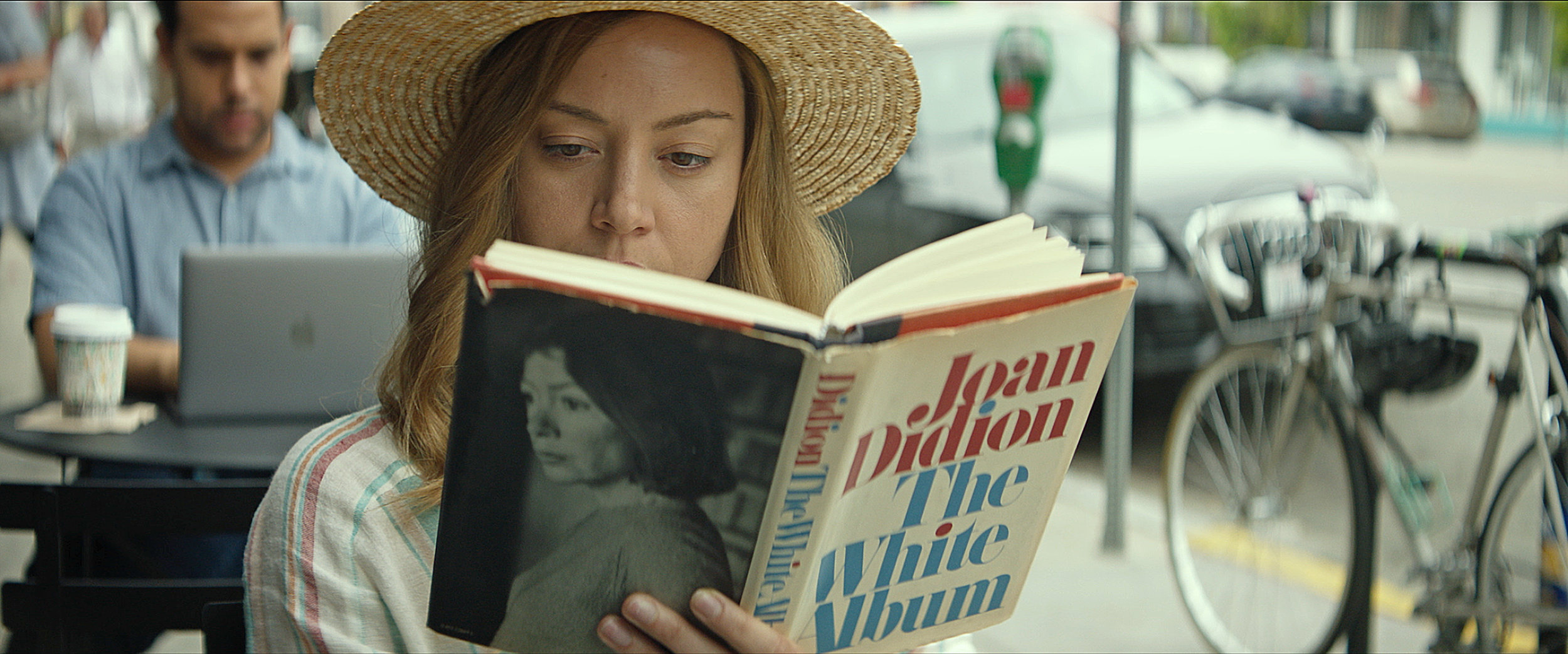 Ingrid (Aubrey Plaza) reads in a public place in INGRID GOES WEST, courtesy of NEON.jpg