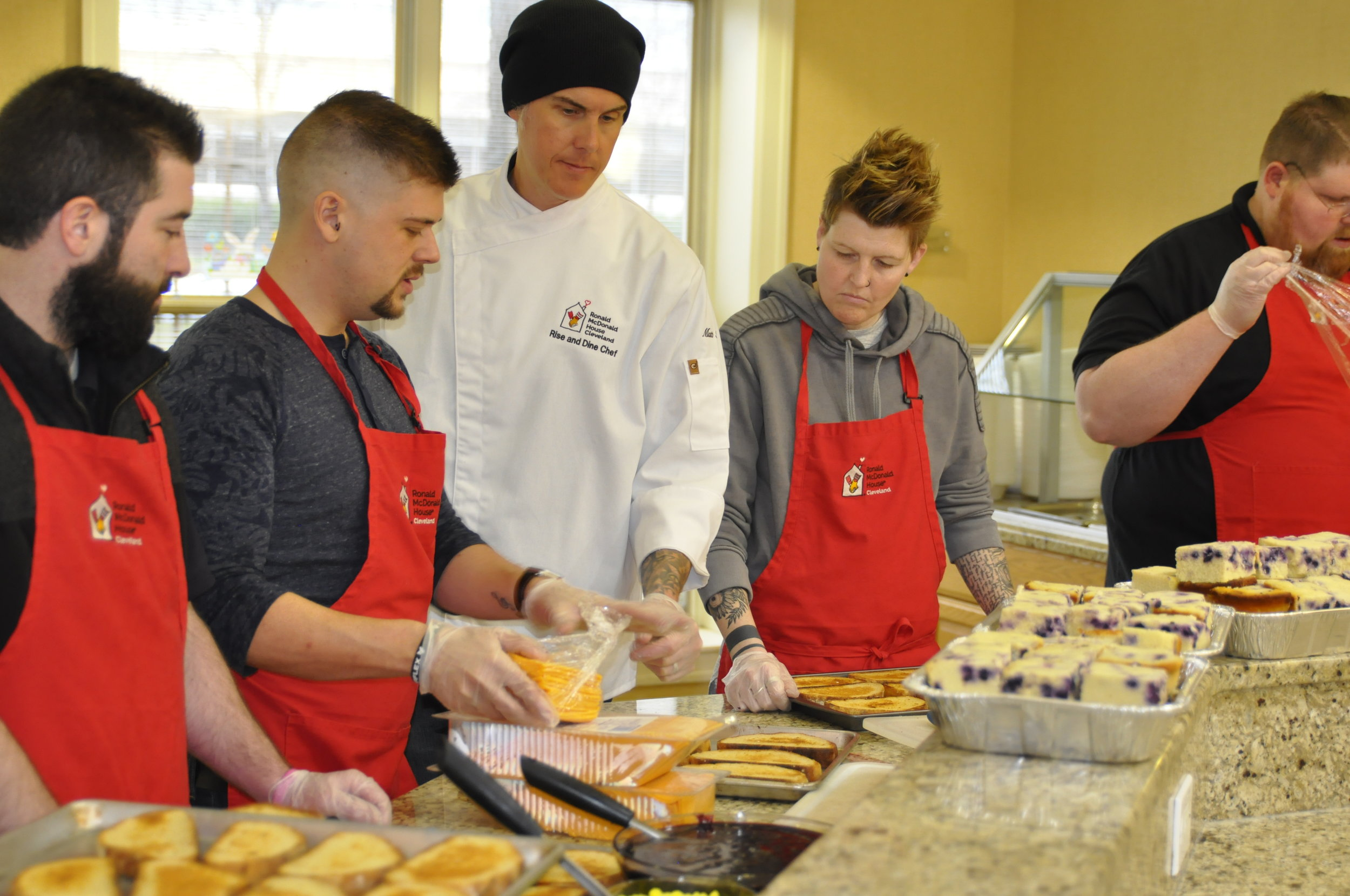 Chef Matt Fish of Melt Bar and Grilled cooks up his famous Parmageddon with volunteers from Verizon Wireless of Mentor during a recent  RISE & Dine .