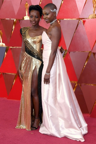 (Left) Lupita Nyong is gorgeous in a one-shoulder gold Atelier Versace Frock and (right) Danai Gurira wearing a Gabriela Hearst.