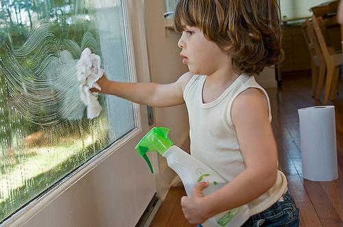 child cleaning window on door