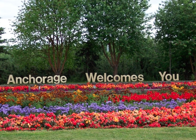"""""""Anchorage Welcomes You"""" sign sits atop a blooming flower bed"""