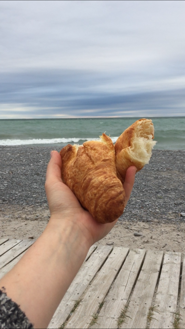 Barbara holds a croissant ripped in half. The lake is in the background, with rolling waves.