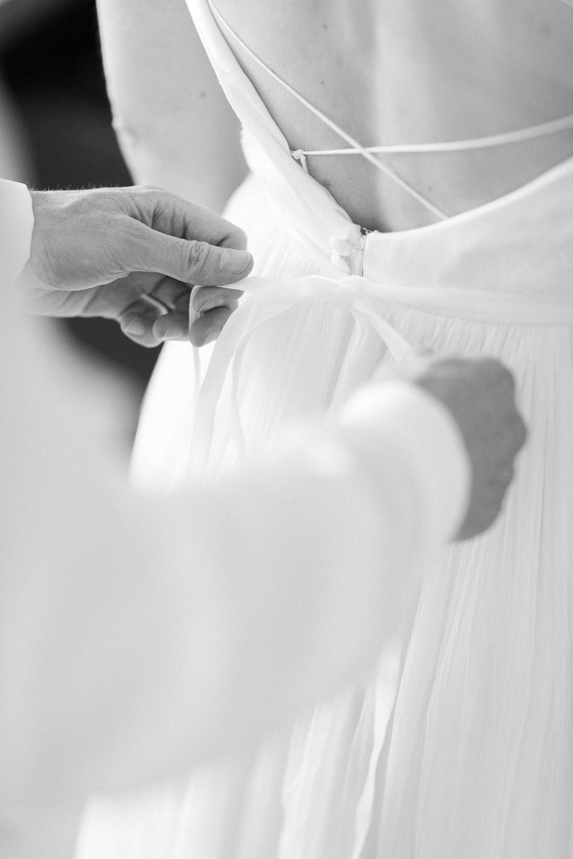 Bräutigam hilft der Braut beim Anziehen des Hochzeitskleides (Hochzeitsreportage in Luzern)