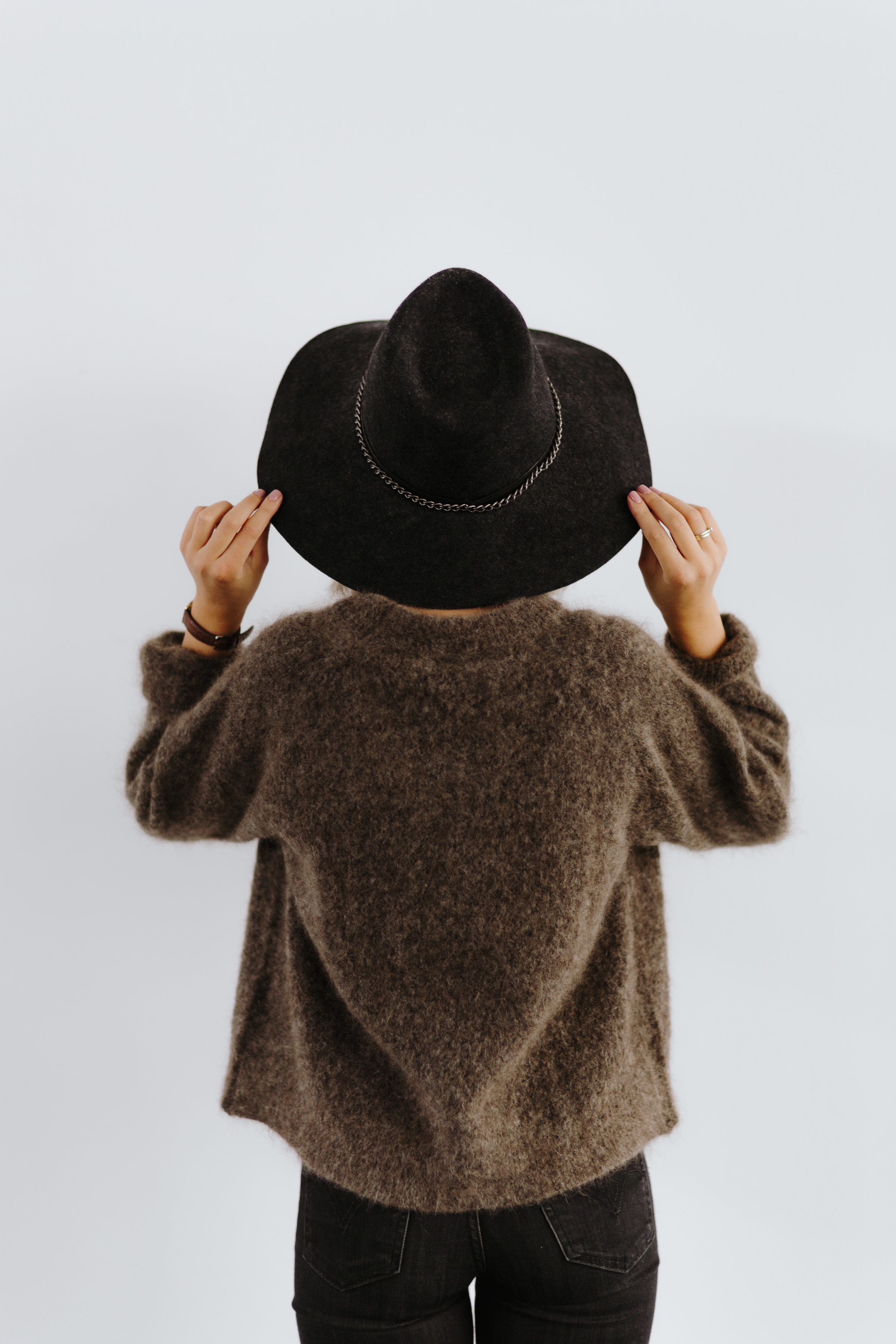 kaboompics_A woman in a brown sweater with a black hat on her head.jpg