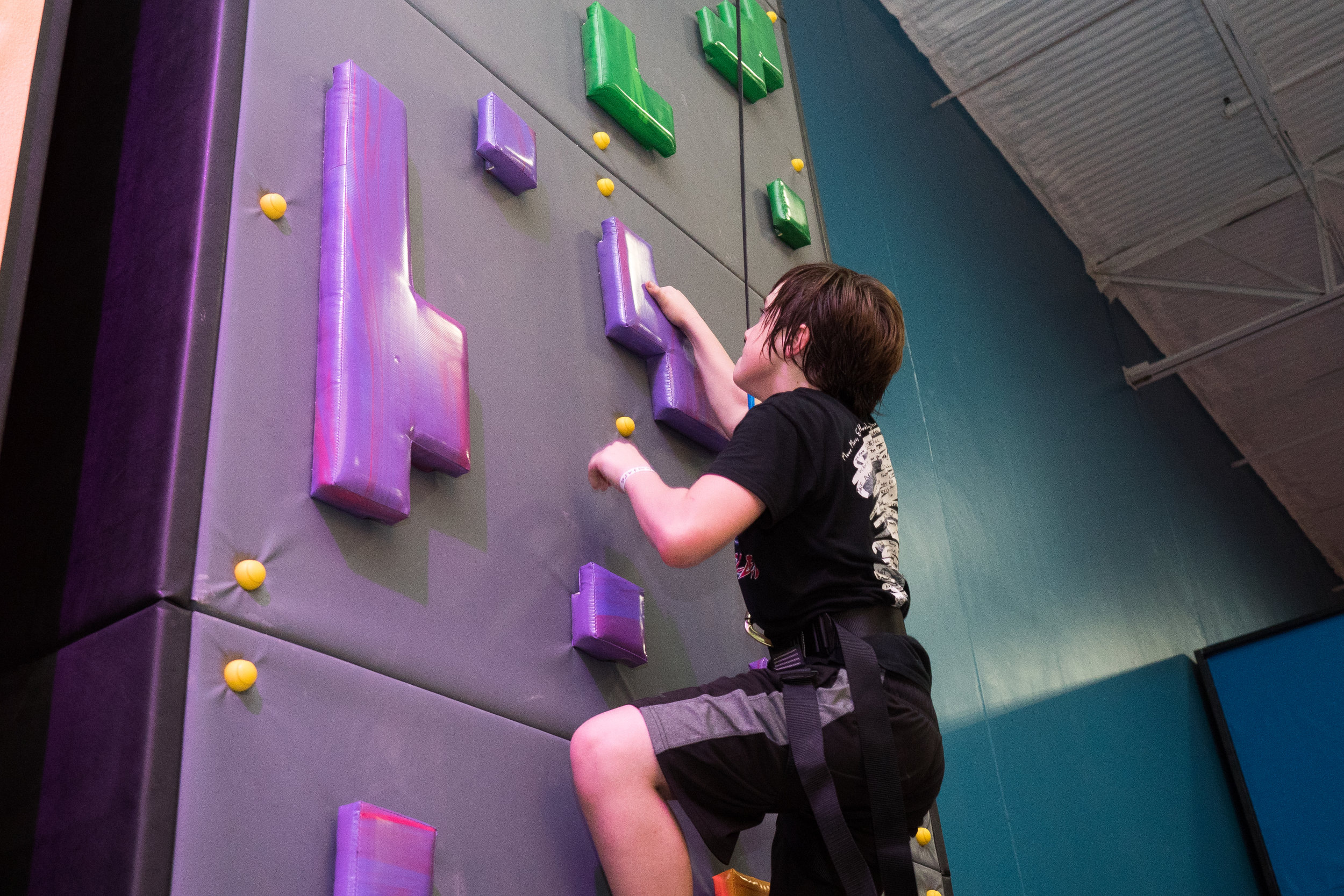 A young boy scales the rock climbing wall.