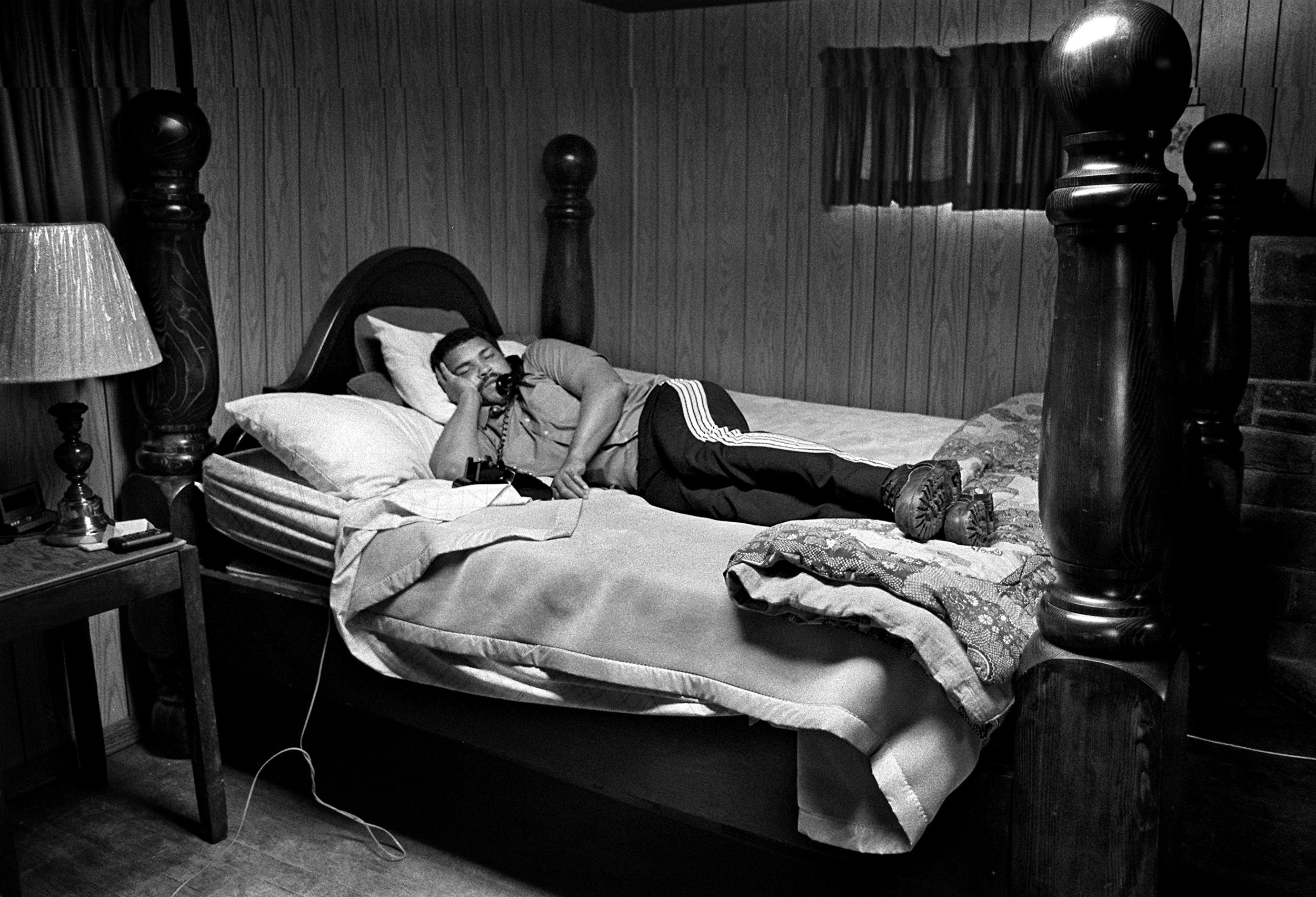 Muhammad Ali, relaxing after a hard session of training. Watching television laying in bed. Photo by Rex Larsen.