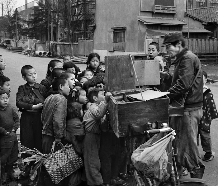 Children gather around a Kamishibai storytime on a street