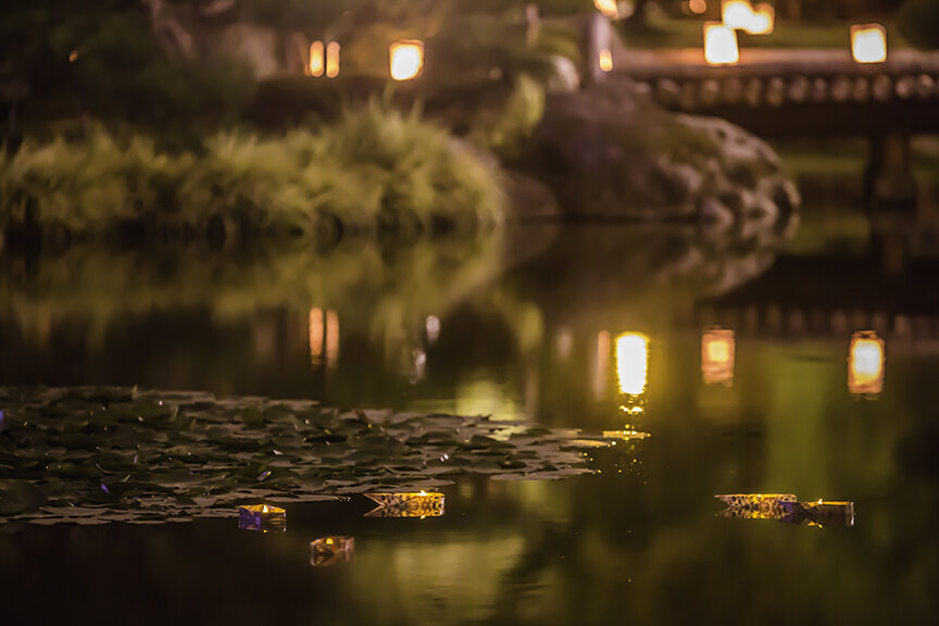 Candle-lit origami boats float near the lily pads (Photo by SlickPix Photography)