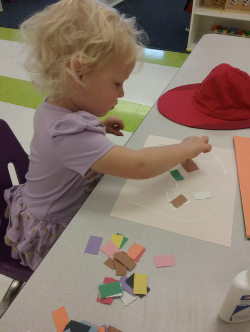 Our art activity this morning was creating a color collage! First we strengthened our fine motor muscles by squeezing glue on our paper with glue bottles. Then we grabbed different colored paper squares and stuck them to the glue. We talked about the colors of our paper as we stuck them on, as well as what our favorite colors were and what color  we would use next.