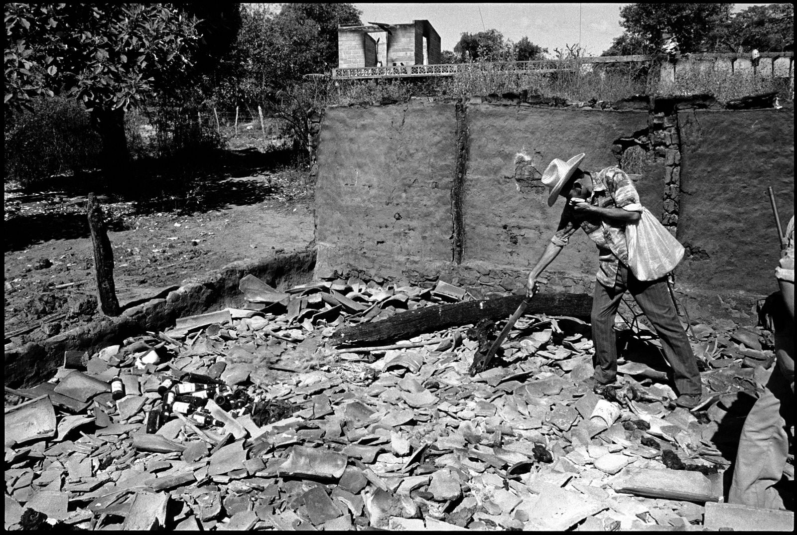 A man looks through the remains of a church in El Mozote in January of 1982, months after the massacre