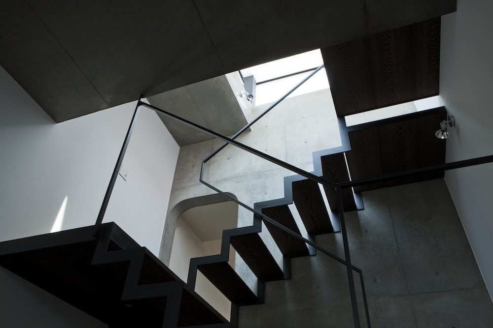 A minimal open stairway of blackened steel and concrete in a building by APOLLO Architects & Associates. Photo by Maseo Nishikawa.