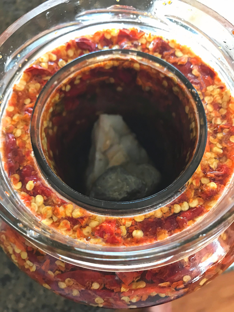 The jelly jar and boiled rock being used as a weight to keep the peppers under the liquid as much as possible...