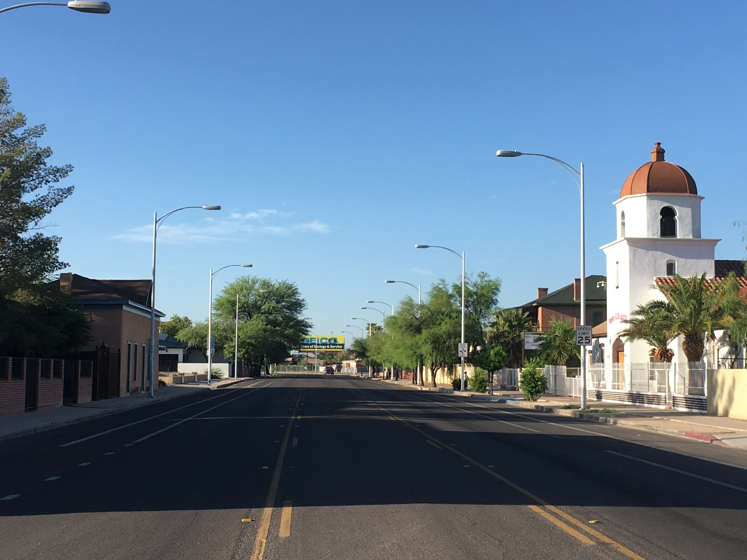 """South Stone Avenue with the Primeria Iglesia Bautista on the right. This was the """"wilderness.""""  The prominent brown adobe with blue trim on the left side was built in the 1870s and was purchased in 1878 by Carlos Ygnacio Velasco. His family lived in the back and the front was the office of his newspaper, El Fronterizo.  One of the neighborhood's most iconic buildings, the Stone Avenue synagogue, was built in 1910. You cannot see it in this photo, but it's on the right side in the next block south. Now called the Jewish History Museum, it was the first synagogue in Arizona."""