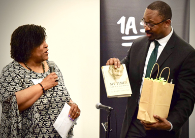 "GSLABJ president Carol Daniel gives Joshua Johnson a ""welcome to St. Louis"" gift."